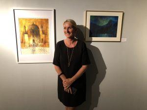 Ellen Hegg foran to av sine bilder som man finner på utstillingen